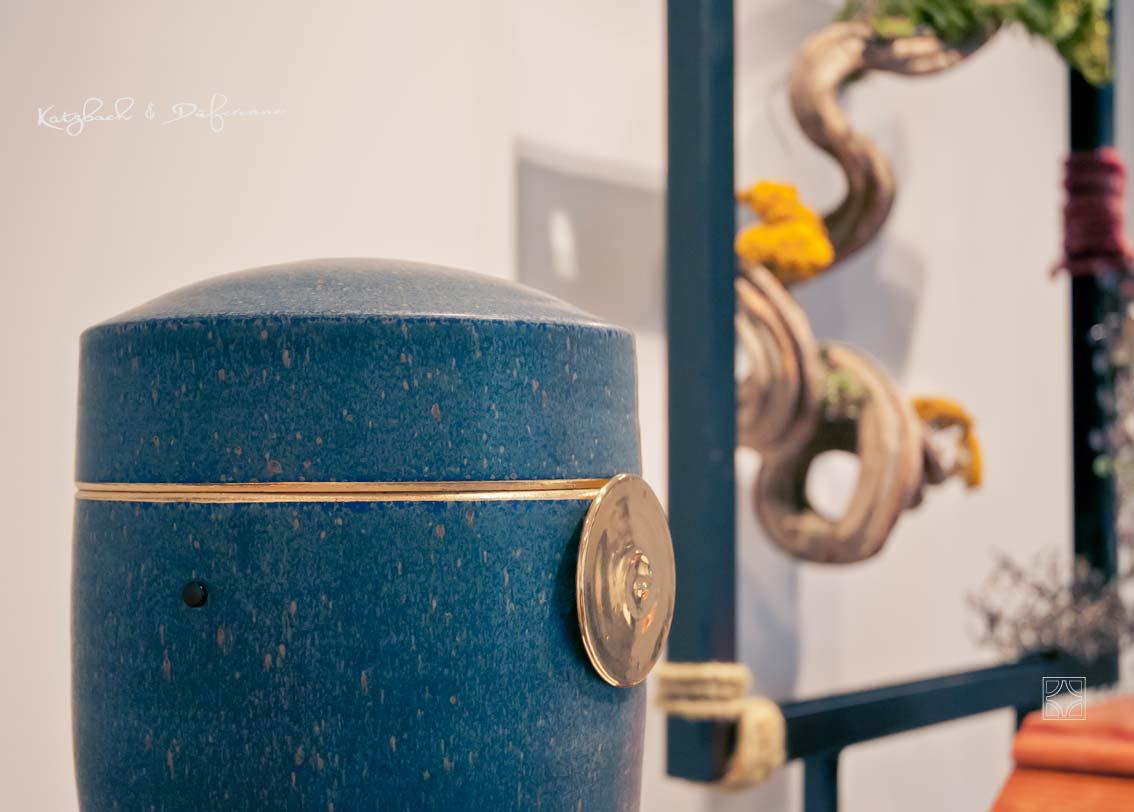 Blick in die Urnenausstellung von Katzbach & Düferenne in Solingen. Keramikurne mit Gold.