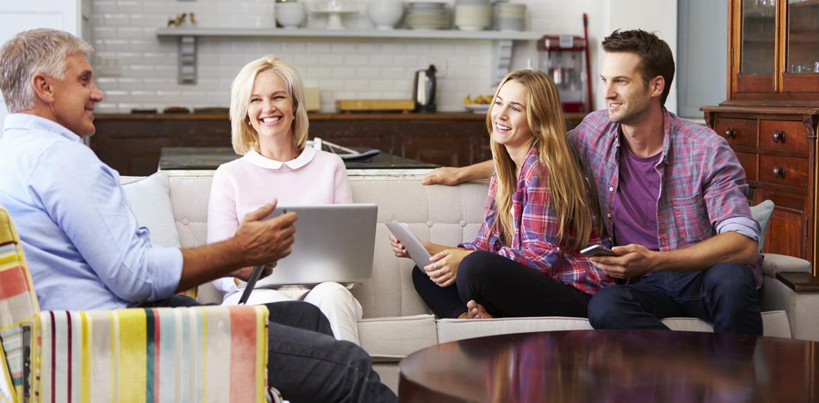 Familie sitzt zusammen und nutzt digitale Medien.