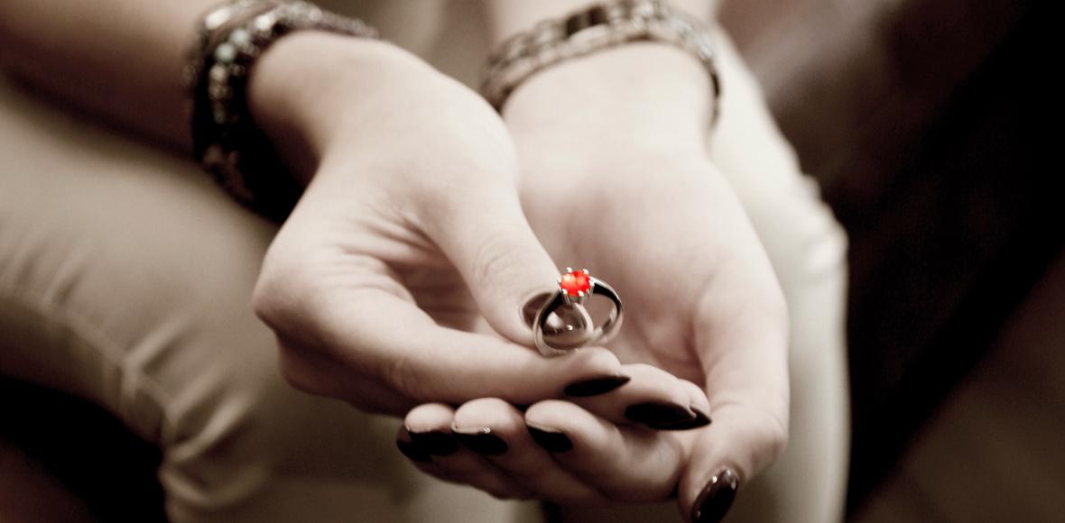 Frauenhände halten Ring mit Mevisto Stein aus oder Asche